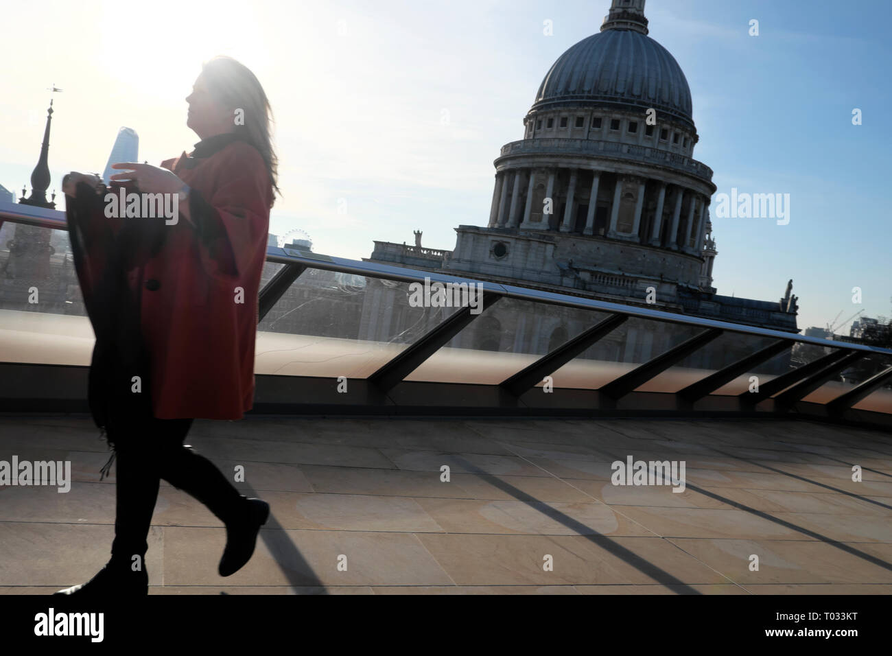 Woman walking on Millennium Bridge with a view of St Pauls Cathedral from One New Change in the City of London UK  KATHY DEWITT - Stock Image
