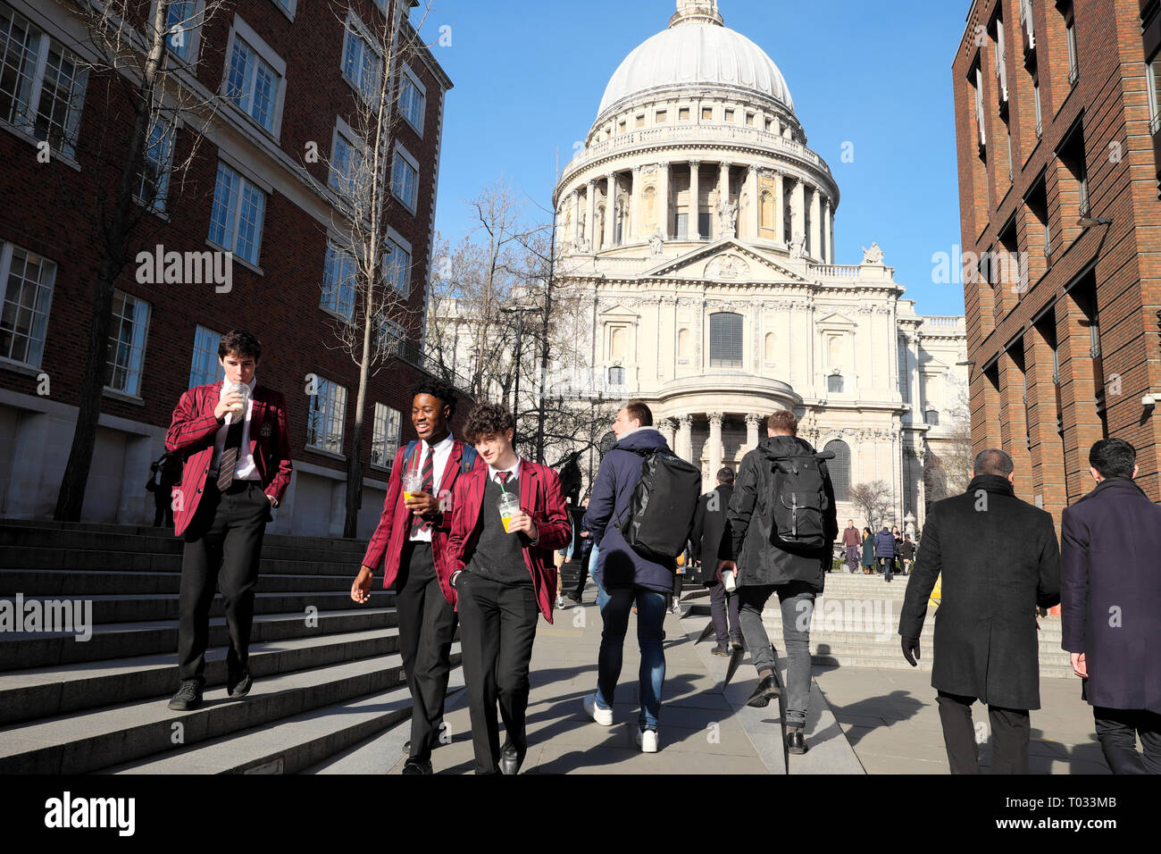 City of London school boys pupils students in uniform enjoying sunshine at lunchtime near St Pauls Cathedral in London England UK  KATHY DEWITT - Stock Image