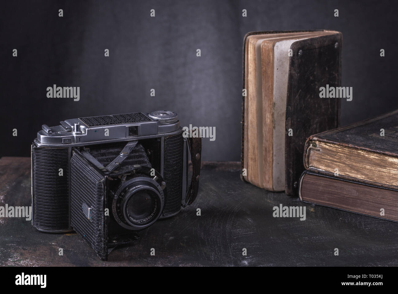 A historic camera with three old books on a black background in a room by the wall. Stock Photo