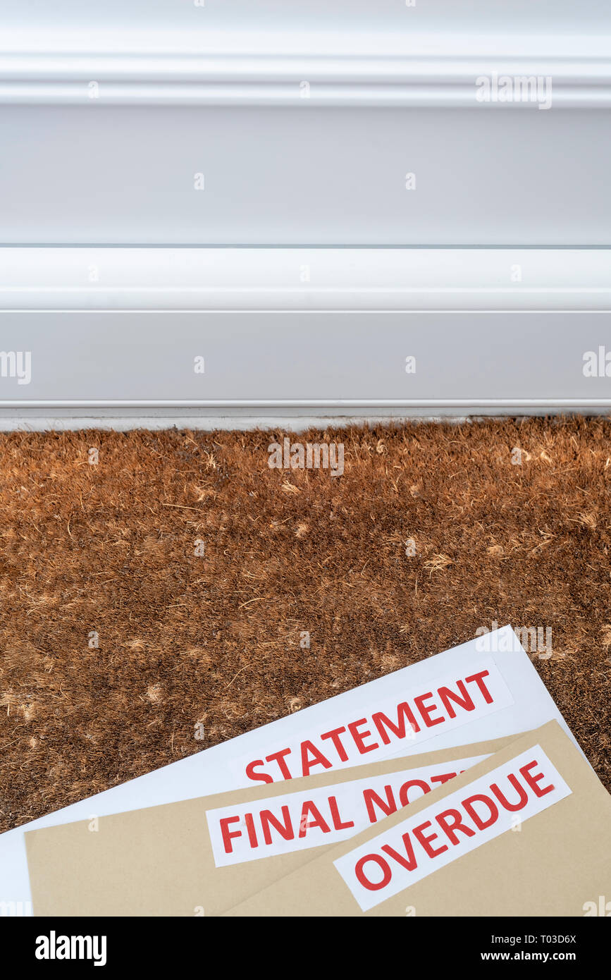 Overdue statements on a door mat. Financial crisis, trying to deal with debt. - Stock Image