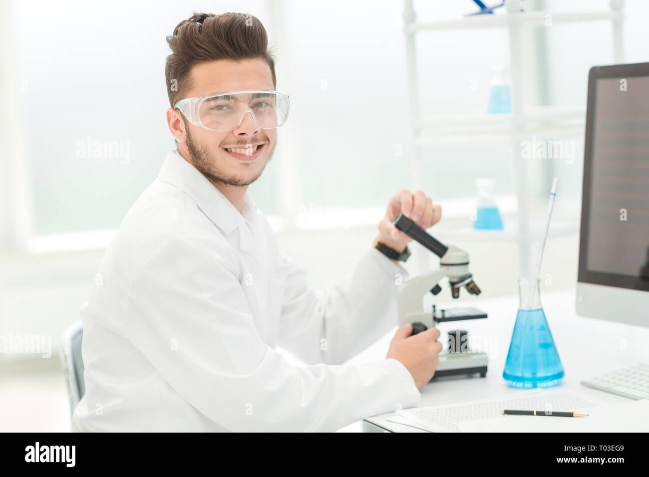 modern scientist sitting at his Desk in the laboratory - Stock Image