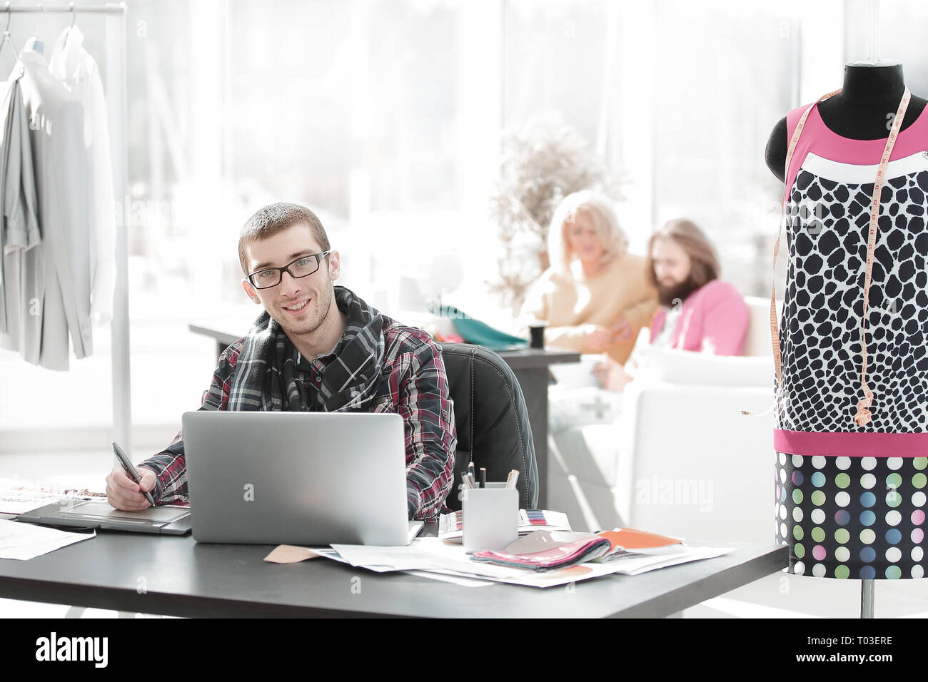 designer using laptop and graphics tablet to create sketches of new clothes - Stock Image
