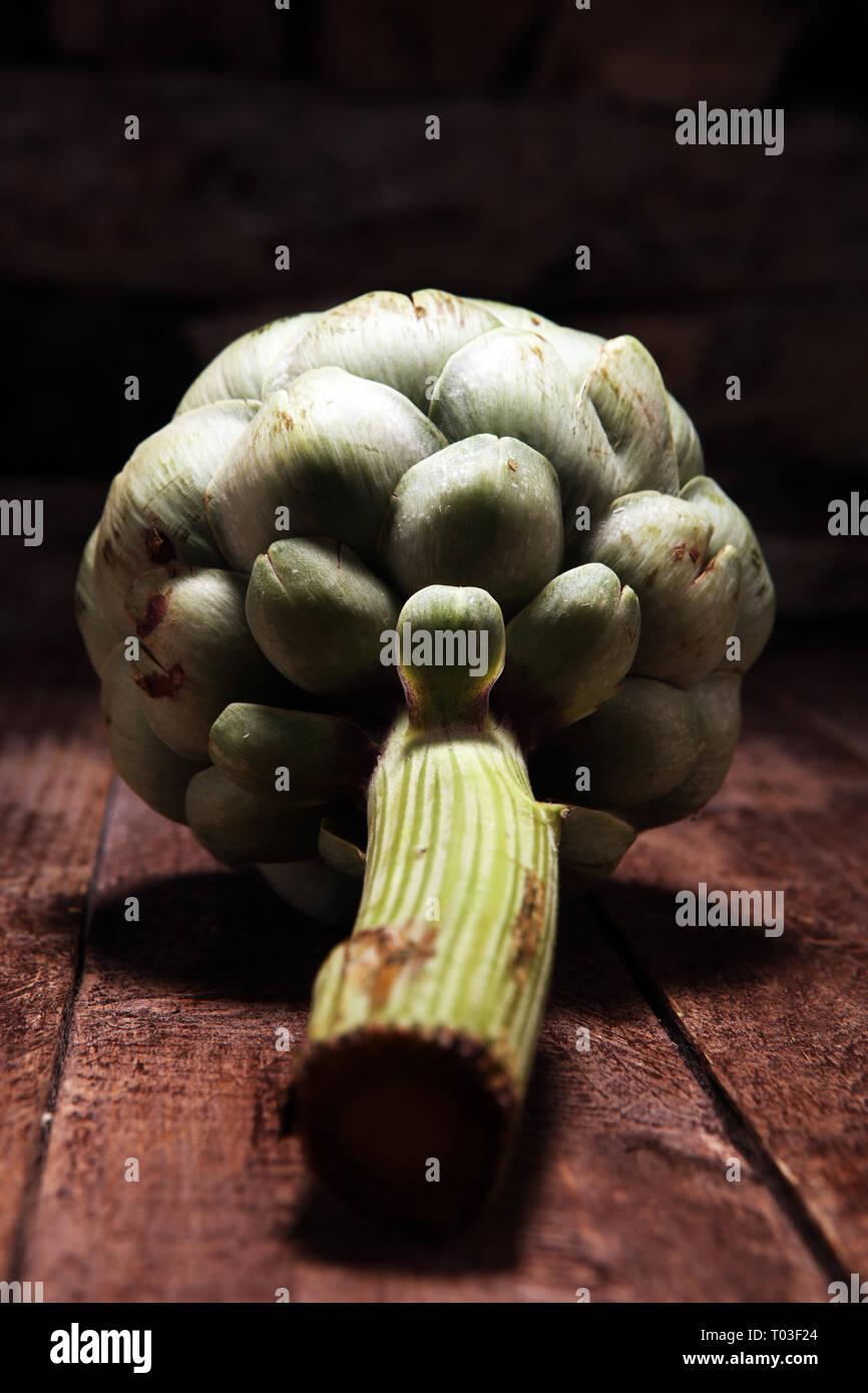 artichokes on old rustic background. fresh organic artichoke flower Stock Photo