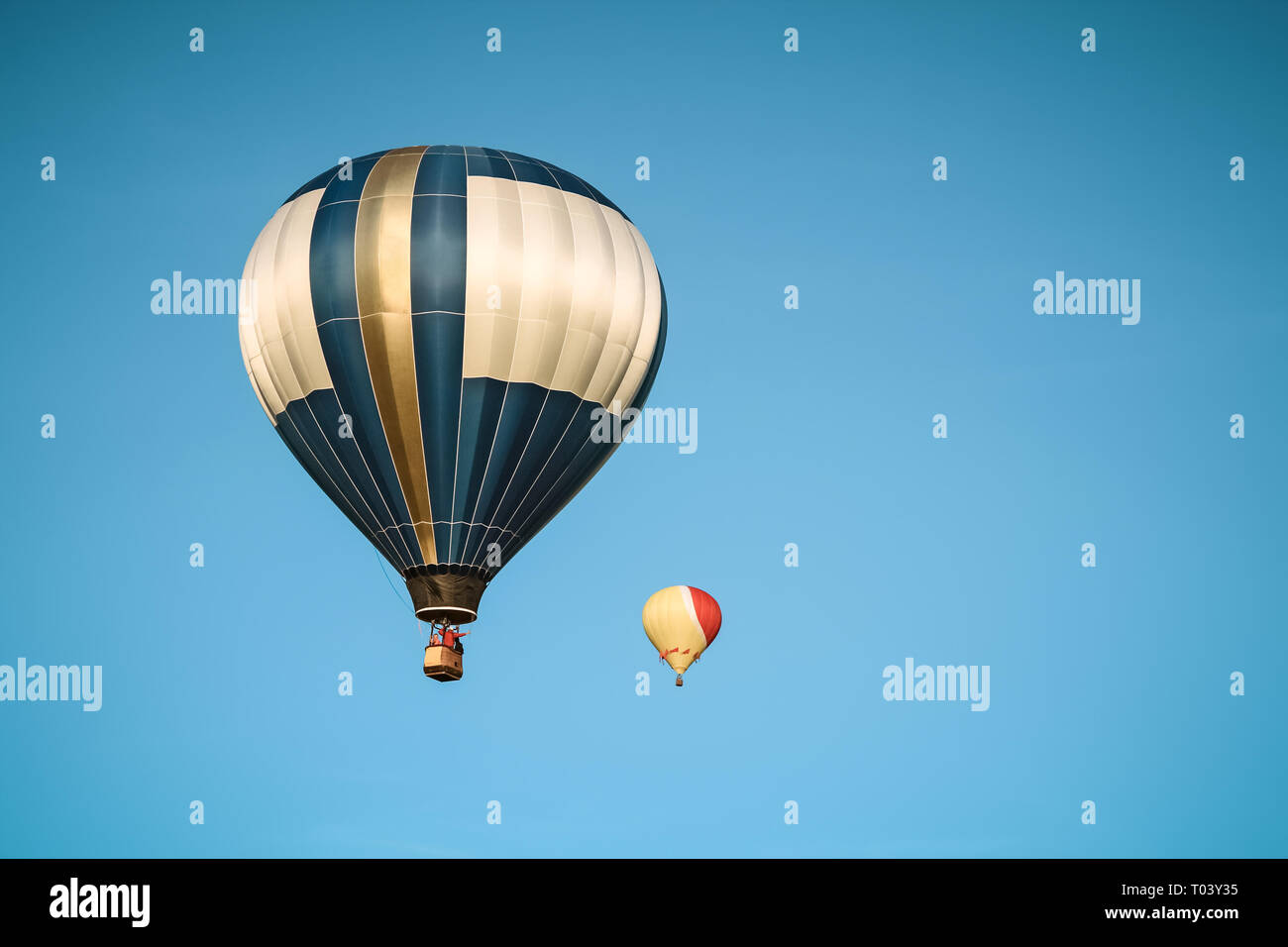 Two hot air balloons in the clear blue sky during a festival. Stock Photo