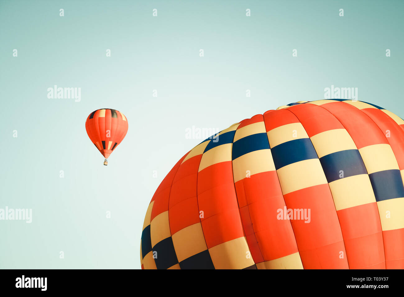 Two vibrant hot air balloons in clear sky, one close and one far. Stock Photo