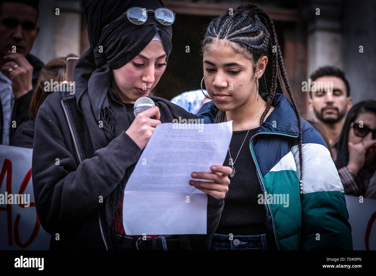 Two young migrant women are seen during the reading of the manifesto. Around 300 people have gather to condemn the racism and discrimination after a racist attack carried out to a house of a young migrant after a fight between young migrants and young residents in Castelldefels area in Barcelona. - Stock Image