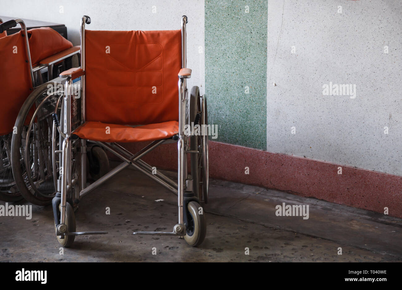 supporting wheelchairs for elderly, senior citizen, disabled in corner background, used when walking is difficult or impossible due to illness, injury - Stock Image