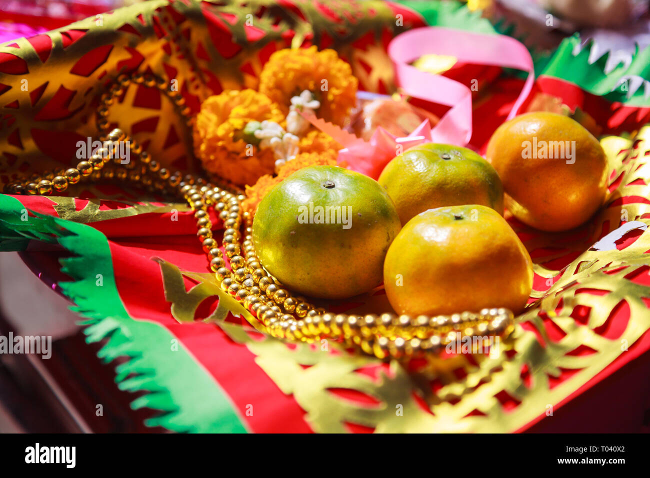 Orange Fruit, Rosary, Flower and Prayer Flag in Chinese Buddhist Temple, material offerings of traditional Mahayana Buddhist devotional practices for  - Stock Image