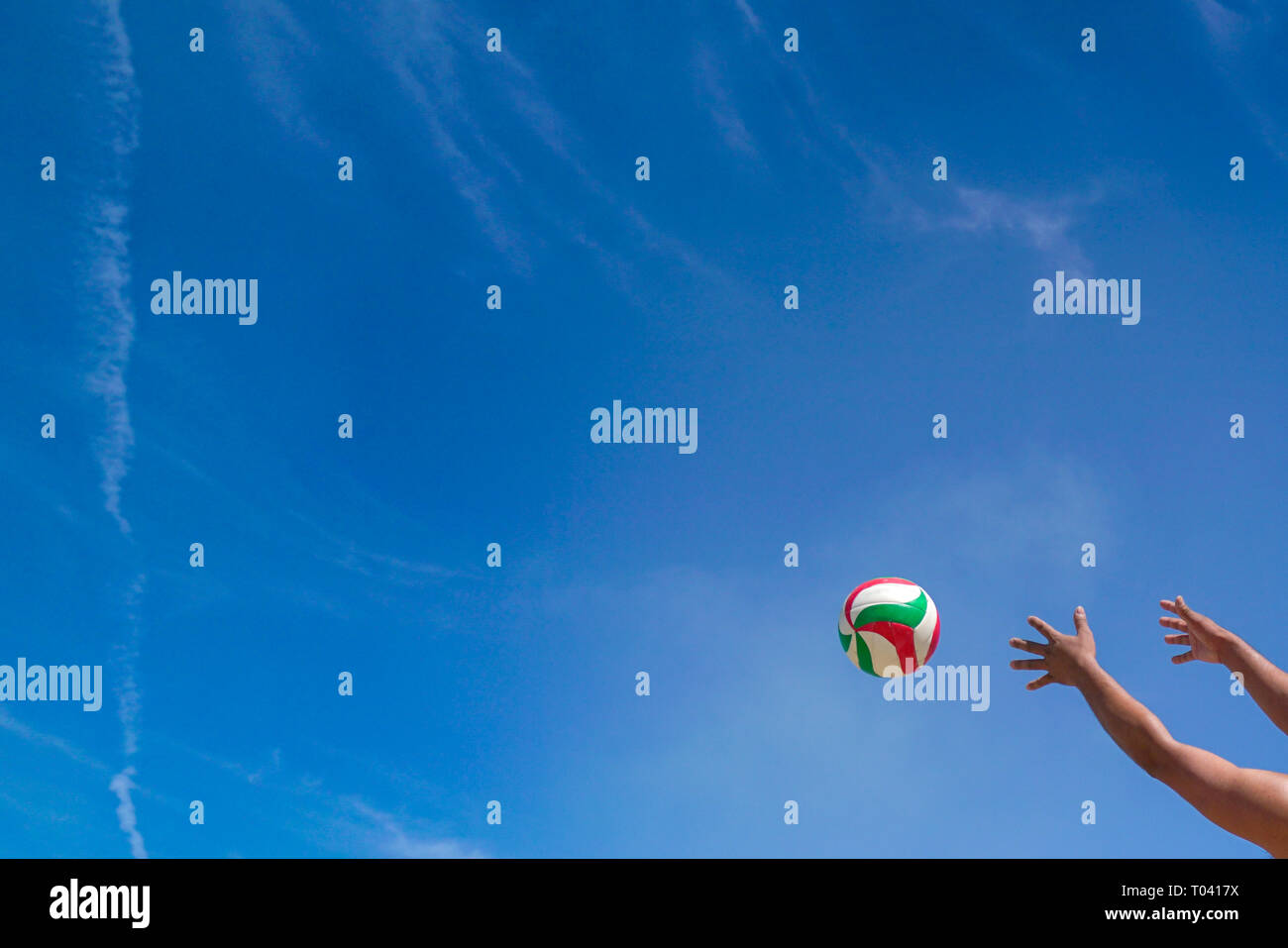 Hands stretch out to catch a ball with sky background, with copy space - Stock Image