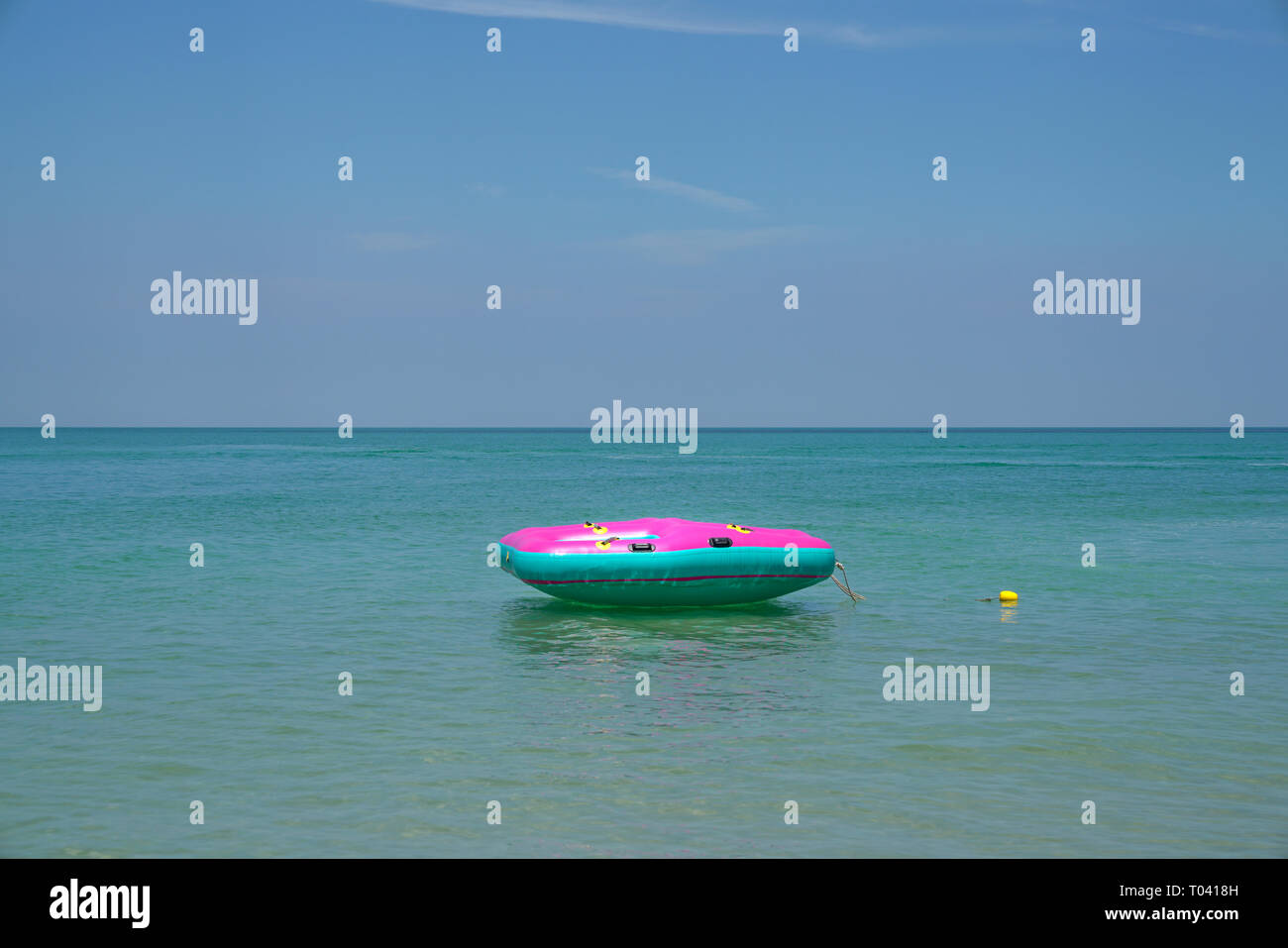 Summer or vacation concept, Inflatable ring or lilo floating in the sea by the beach - Stock Image