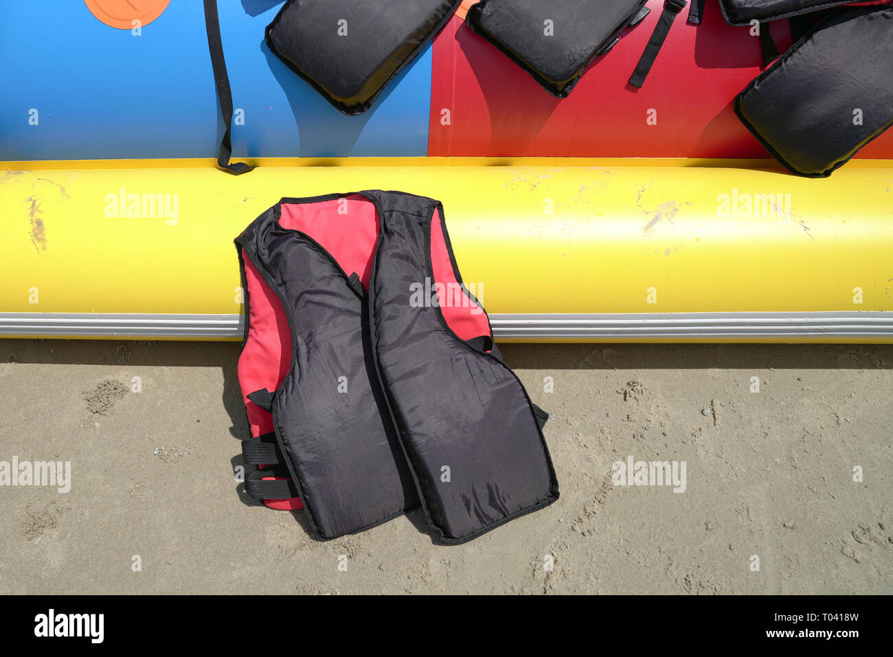 Life jacket by the side of a colorful banana boat with copy space - Stock Image