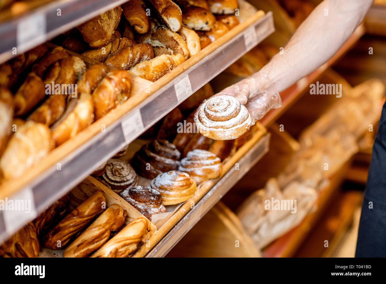 Taking sweet bun from the shelves in the supermarket, close-up view - Stock Image