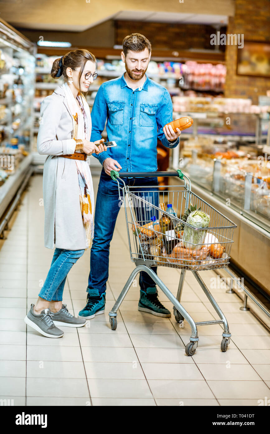 Young Couple Buying Food Standing With Shopping Cart In The