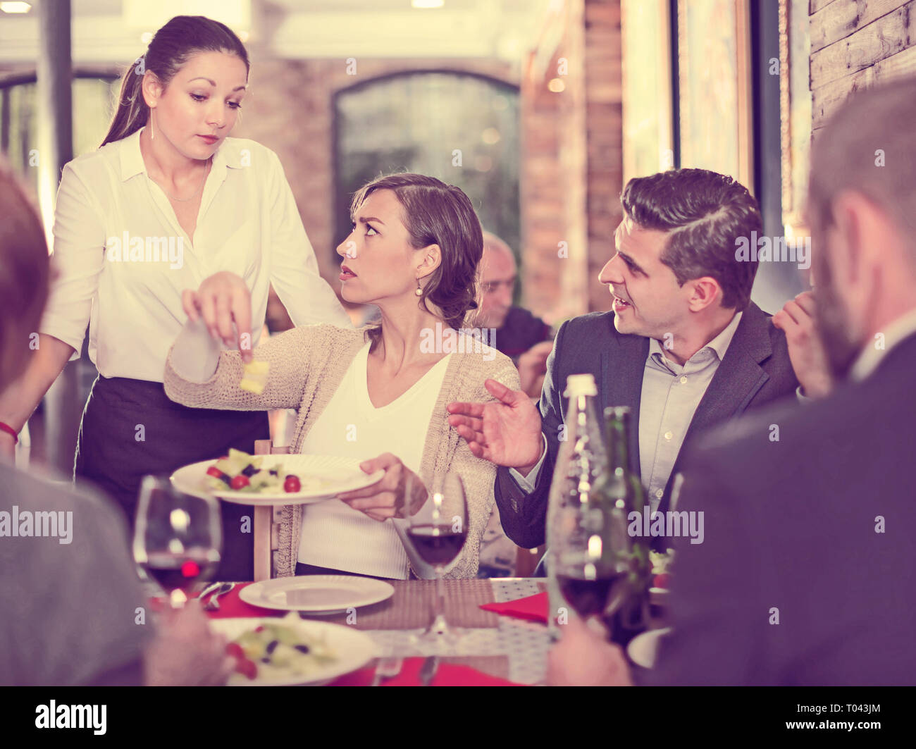 Company of people expressing dissatisfaction with the waitress about food - Stock Image