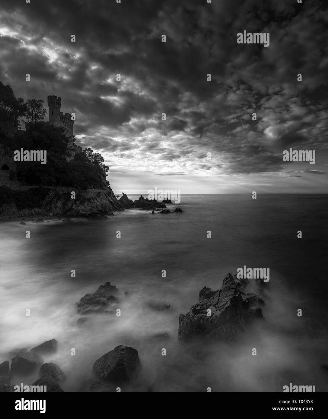 Black and white, long exposure capture of castle on a hill by the sea, Cala Frares, Lloret de Mar, Spain - Stock Image