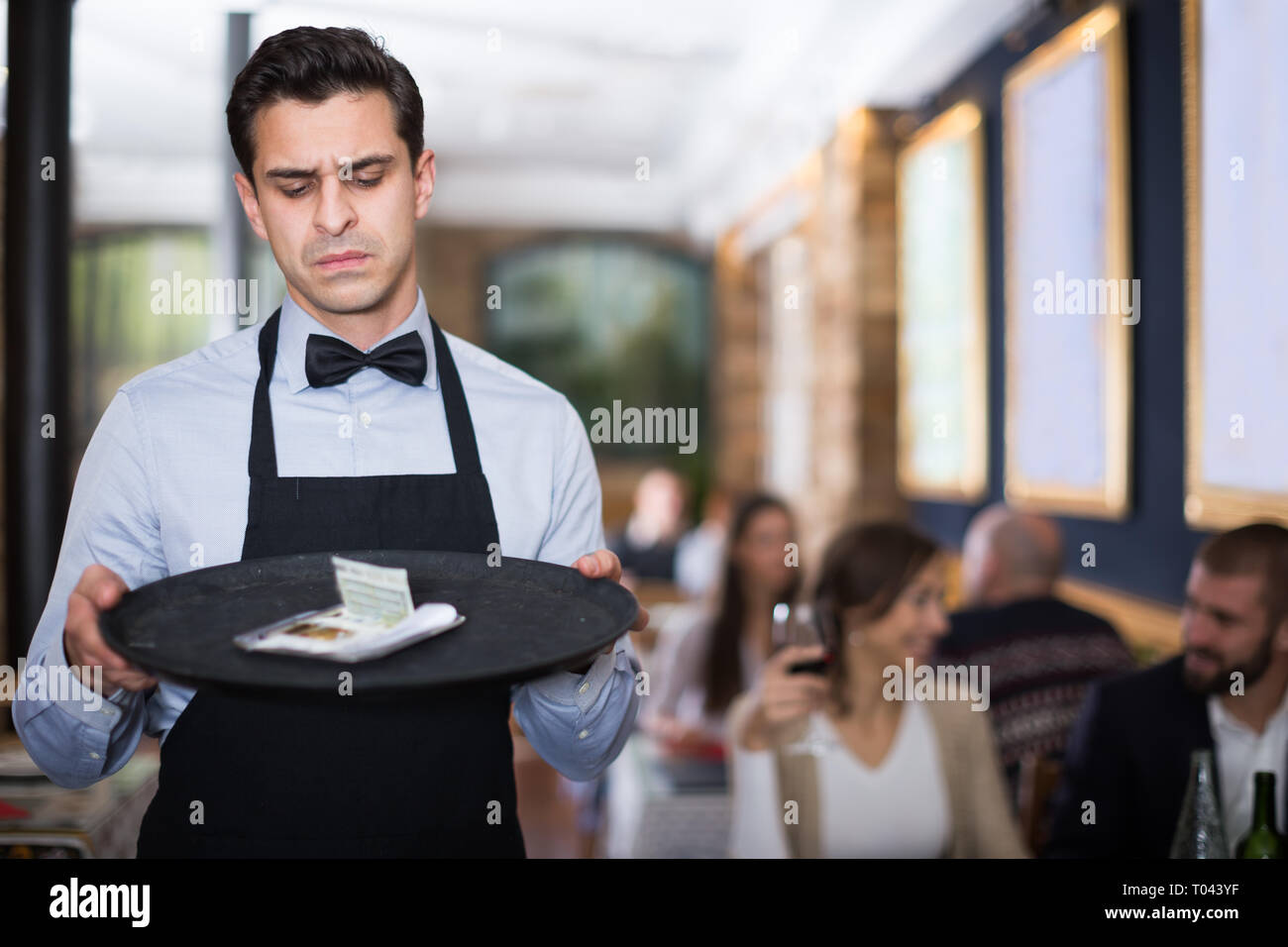 frustrated waiter looking at a tip on a tray in a cafe - Stock Image