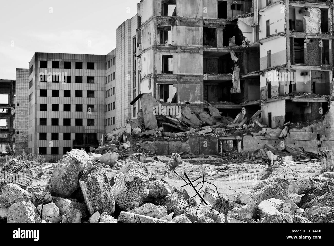 A pile of concrete debris on the background of a large destroyed building. Background. The concept of the consequences of human activities. Black and  - Stock Image