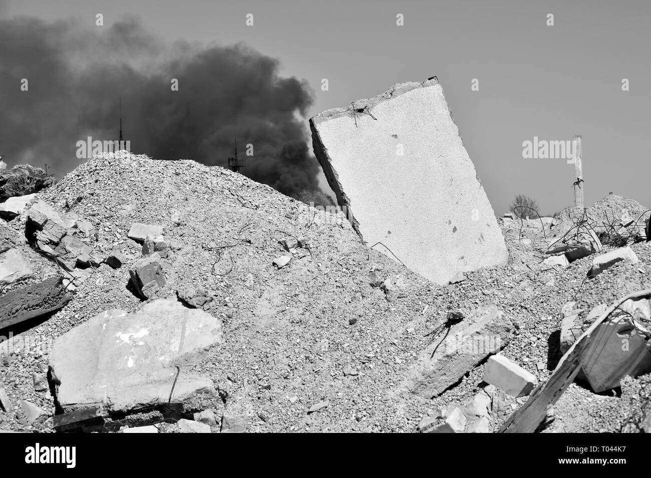 Concrete slab stuck in the ground against the background of a Smoking electrical substation. A symbol of the devastation of war. Background, place of  - Stock Image