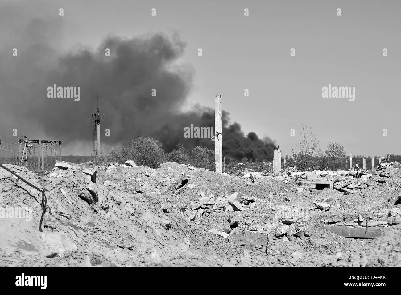A pile of concrete rubble with protruding rebar on the background of thick black smoke in the blue sky. Background. The concept of the consequences of - Stock Image