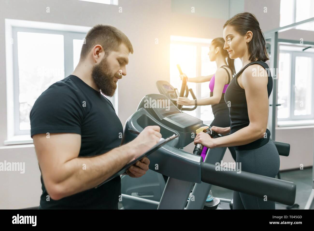 Young smiling fitness women with personal trainer an adult athletic man on treadmill in the gym. Sport, teamwork, training, healthy lifestyle concept. - Stock Image