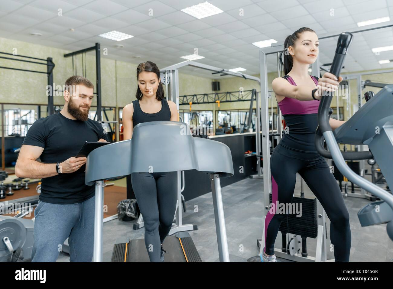 Young smiling fitness women with personal trainer an adult athletic man on treadmill in the gym. Sport, teamwork, training, healthy lifestyle concept - Stock Image