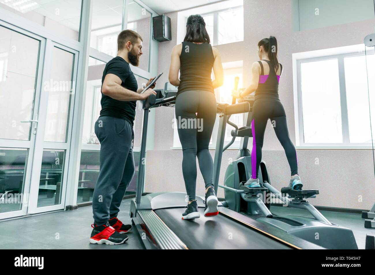 Young athletic women on treadmill, personal instructor coaching and helping client woman. Fitness, sport, training, people concept Stock Photo