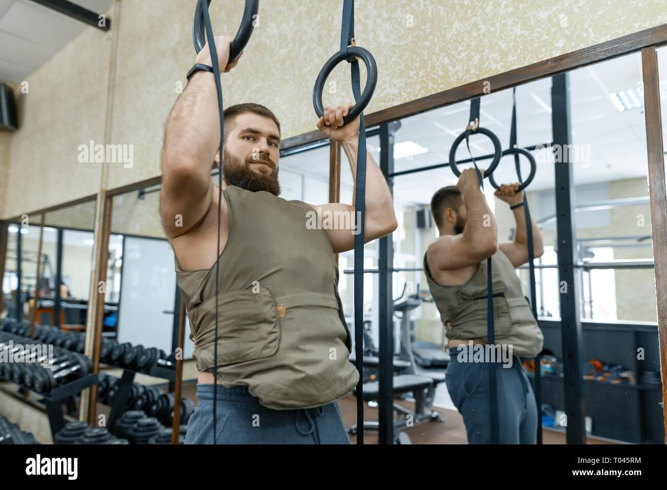 Muscular caucasian bearded man doing exercises dressed in weighted vest in the gym, military style. - Stock Image