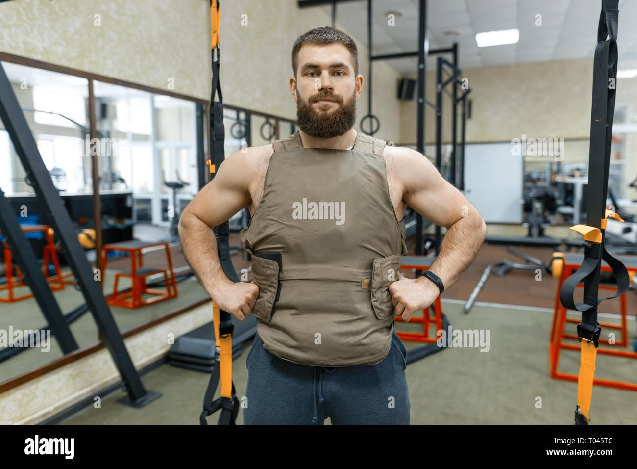 Portrait muscular caucasian bearded adult man in gym, dressed in bulletproof armored vest, military sport. - Stock Image