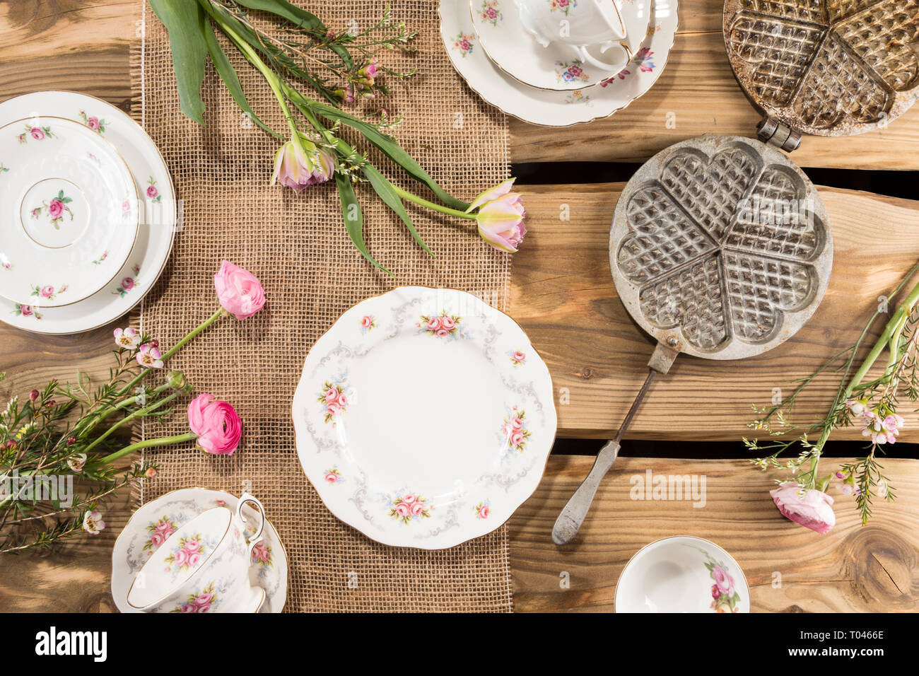 Old romantic porcelain, pink flowers and ancient waffle iron arranged on rustic wood planks. Shot from above, flat lay. Stock Photo