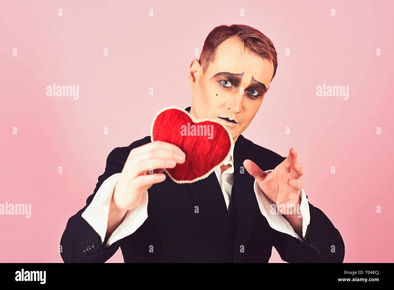 He is sensitive and very poetic. Mime man hold red heart for valentines day. Theatre actor pantomime falling in love. Mime actor with love symbol - Stock Image