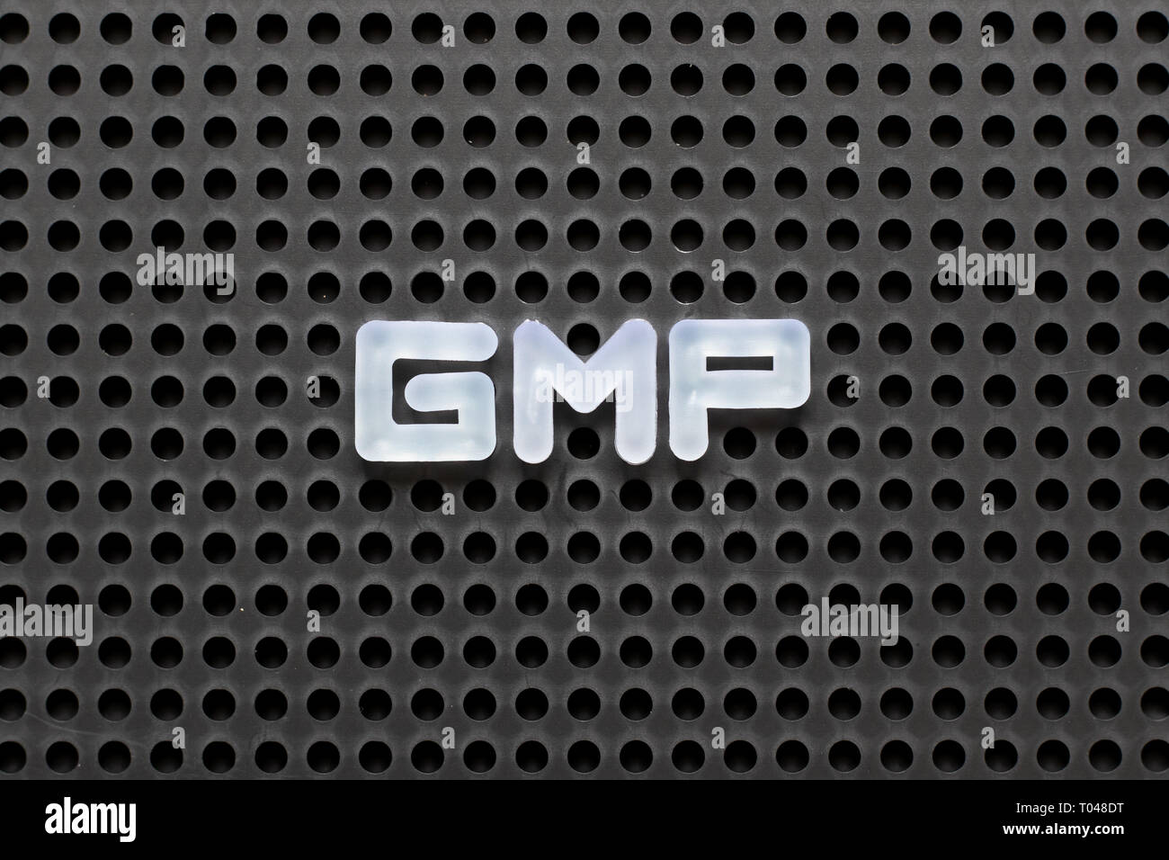 Black color pegboard with white letter in word GMP (Abbreviation of good manufacturing practice) - Stock Image