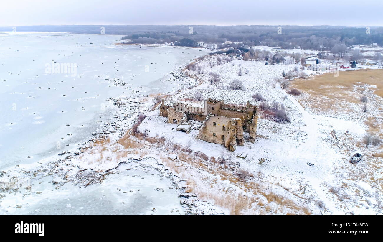 Panoramic view of the Toolse castle in Estonia with lots of snow surrounding the small ruined castle and the frozen sea on a winter season - Stock Image