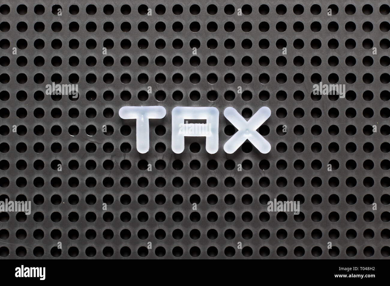 Black color pegboard with white letter in word tax - Stock Image