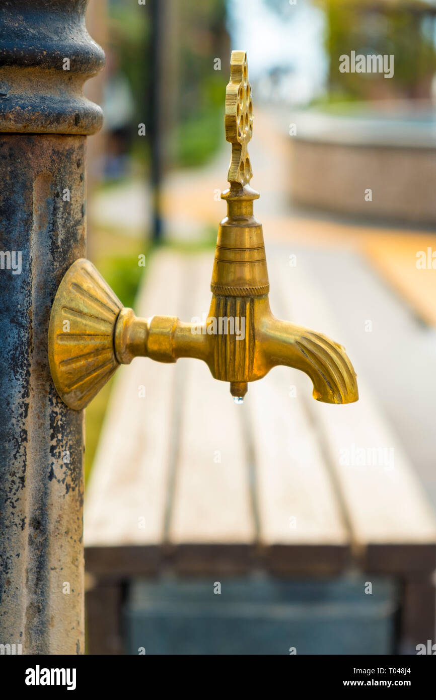 Side view of ornamental water fountain spigot seen in front of a public park bench - Stock Image