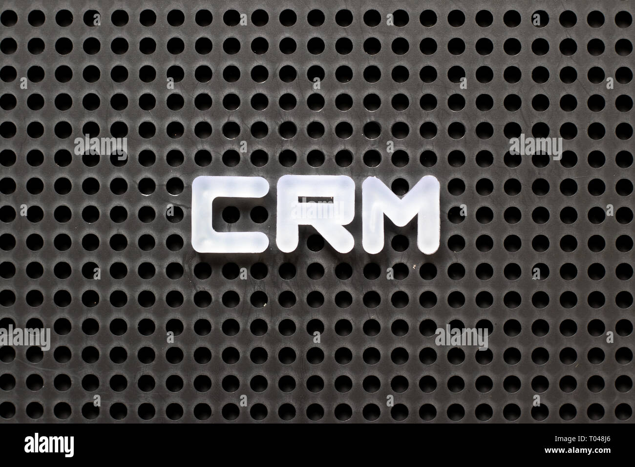 Black color pegboard with white letter in word CRM (Abbreviation of Customer Relationship Management) - Stock Image