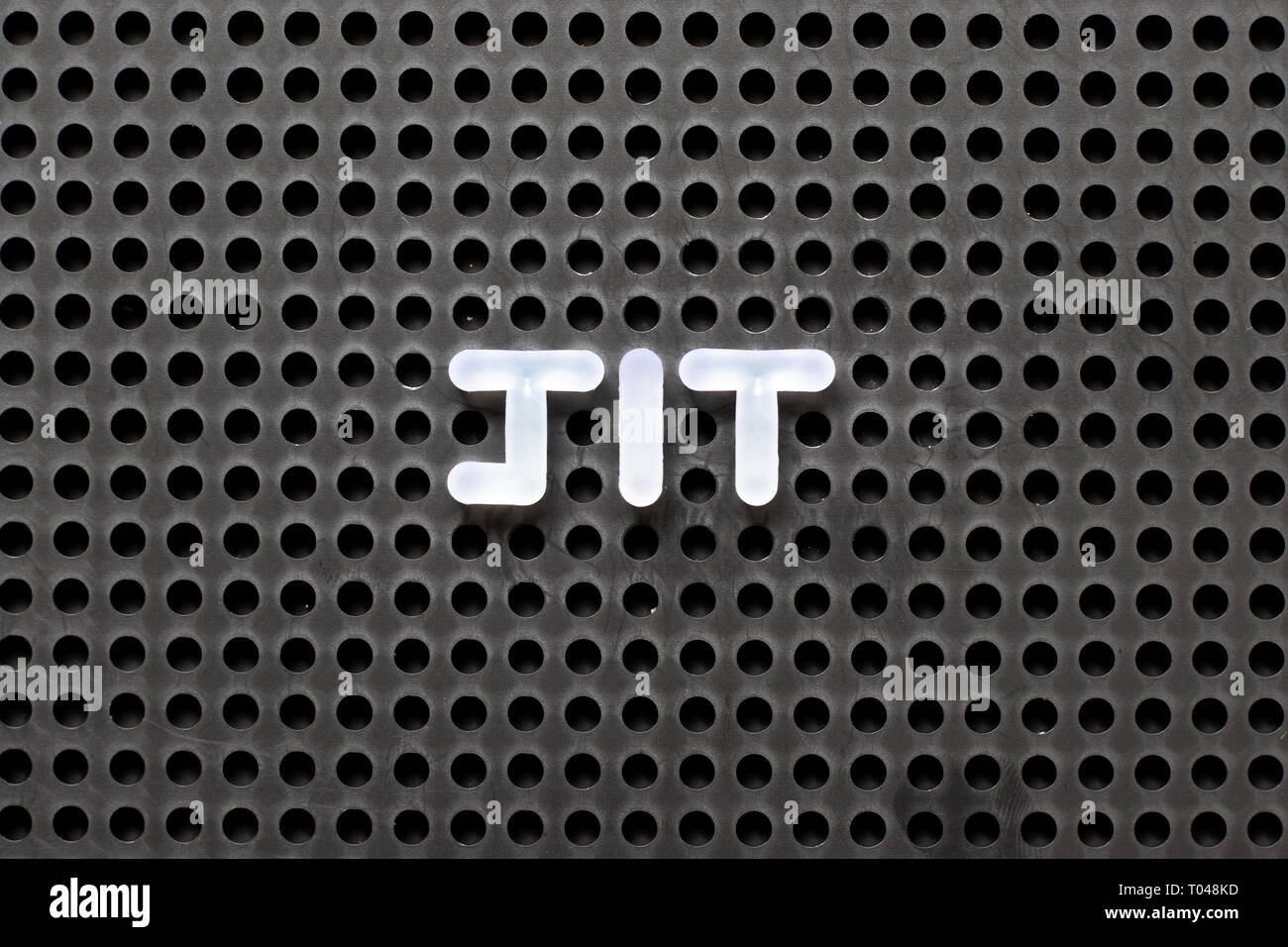 Black color pegboard with white letter in word JIT (abbreviation of just in time) - Stock Image
