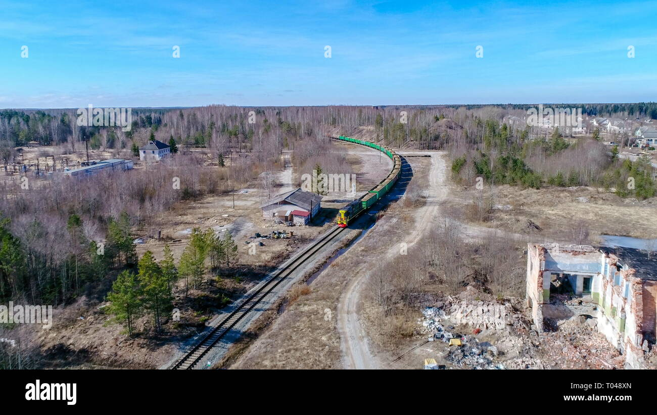 Aerial shot of the ruined house beside the train trail tracks with the running train and the trees all over - Stock Image