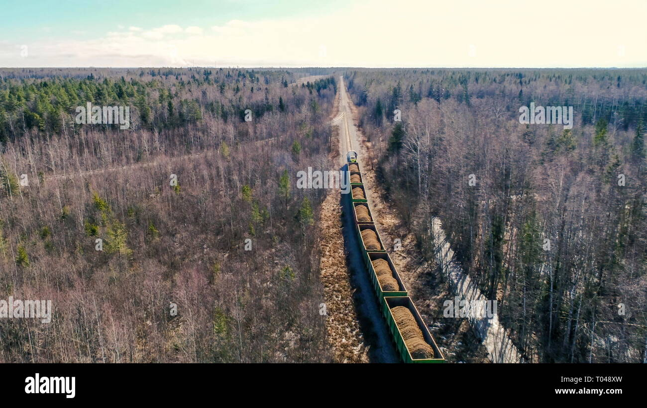 Aerial shot of the trains running on the railtracks with wagons full of sand on a sunny day - Stock Image