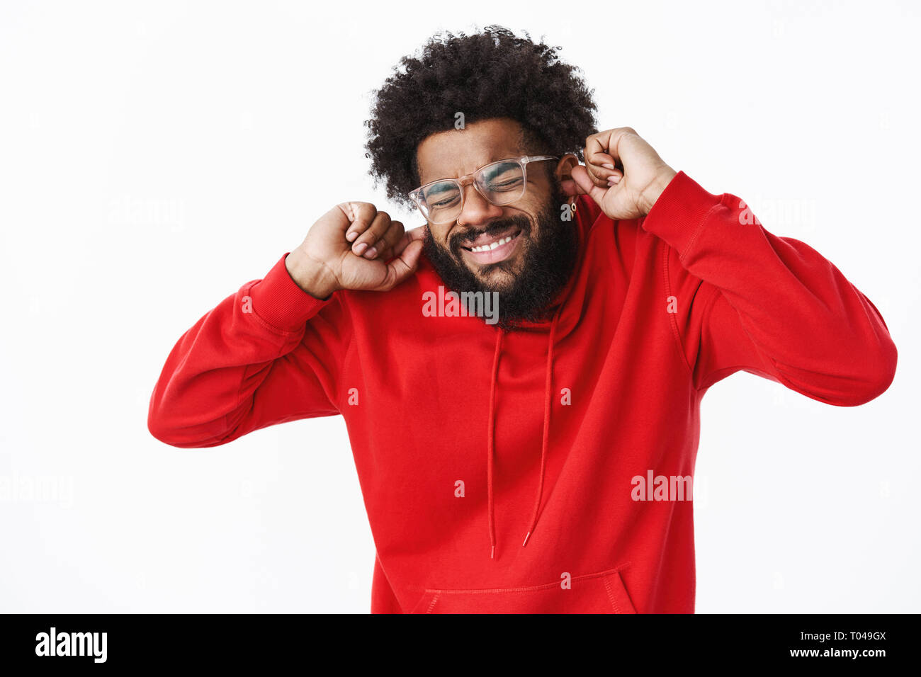African american bearded guy in red hoodie grimacing, close eyes intense and clenching teeth as preparing to loud noise or sound of siren, closing - Stock Image