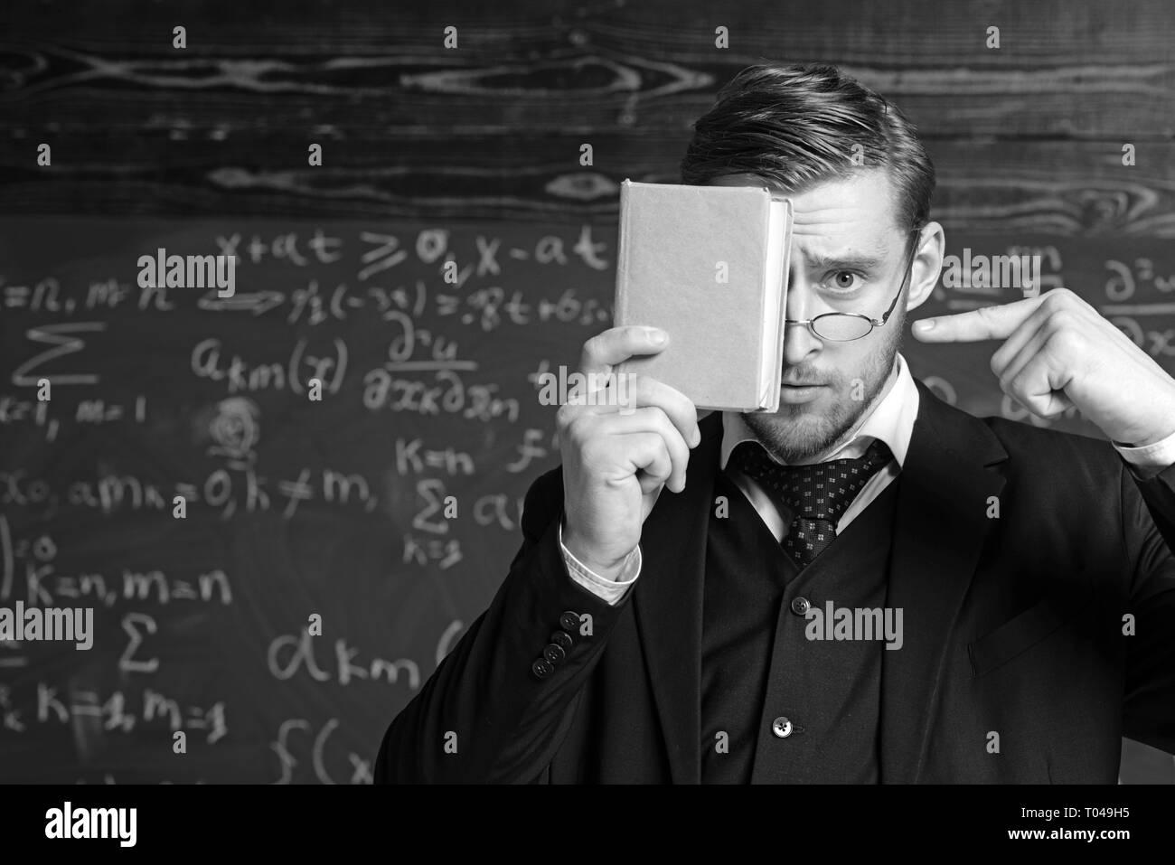 Handsome student in suit covering his face with book while pointing at it with other hand. Closeup portrait of young blond aristocrat with stylish - Stock Image