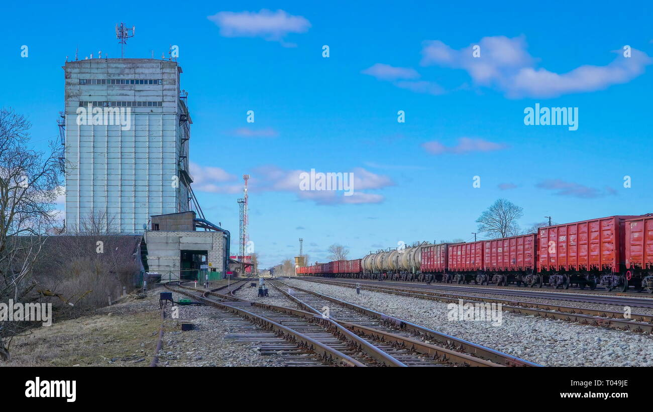 A tall old building near the train railway with the train on standy has loads on the wagon - Stock Image