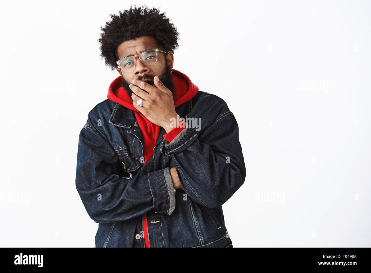 Not impressive nor interesting. Portrait of indifferent african american man watching boring movie wearing glasses, denim jacket over hoodie, yawning - Stock Image