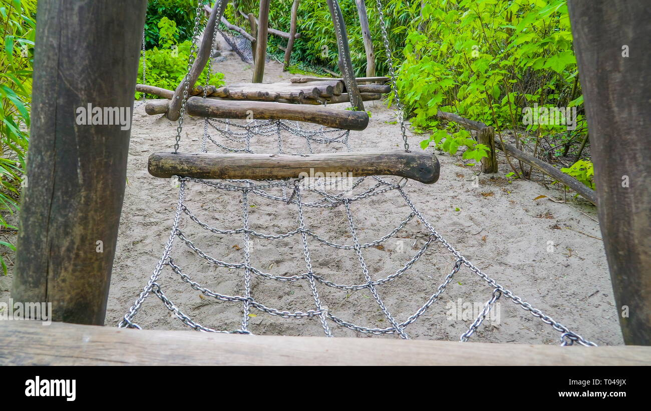 A chain obstacles inside the safari jungle with big logs and chains hanging in the middle of the green plant - Stock Image