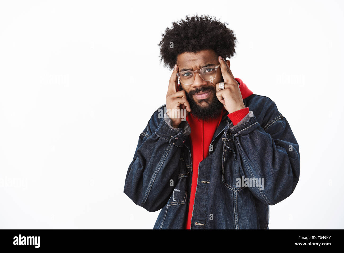 Portrait of confused and frustated sad african american man cannot focus having headache or migraine holding fingers on temples frowning and grimacing - Stock Image