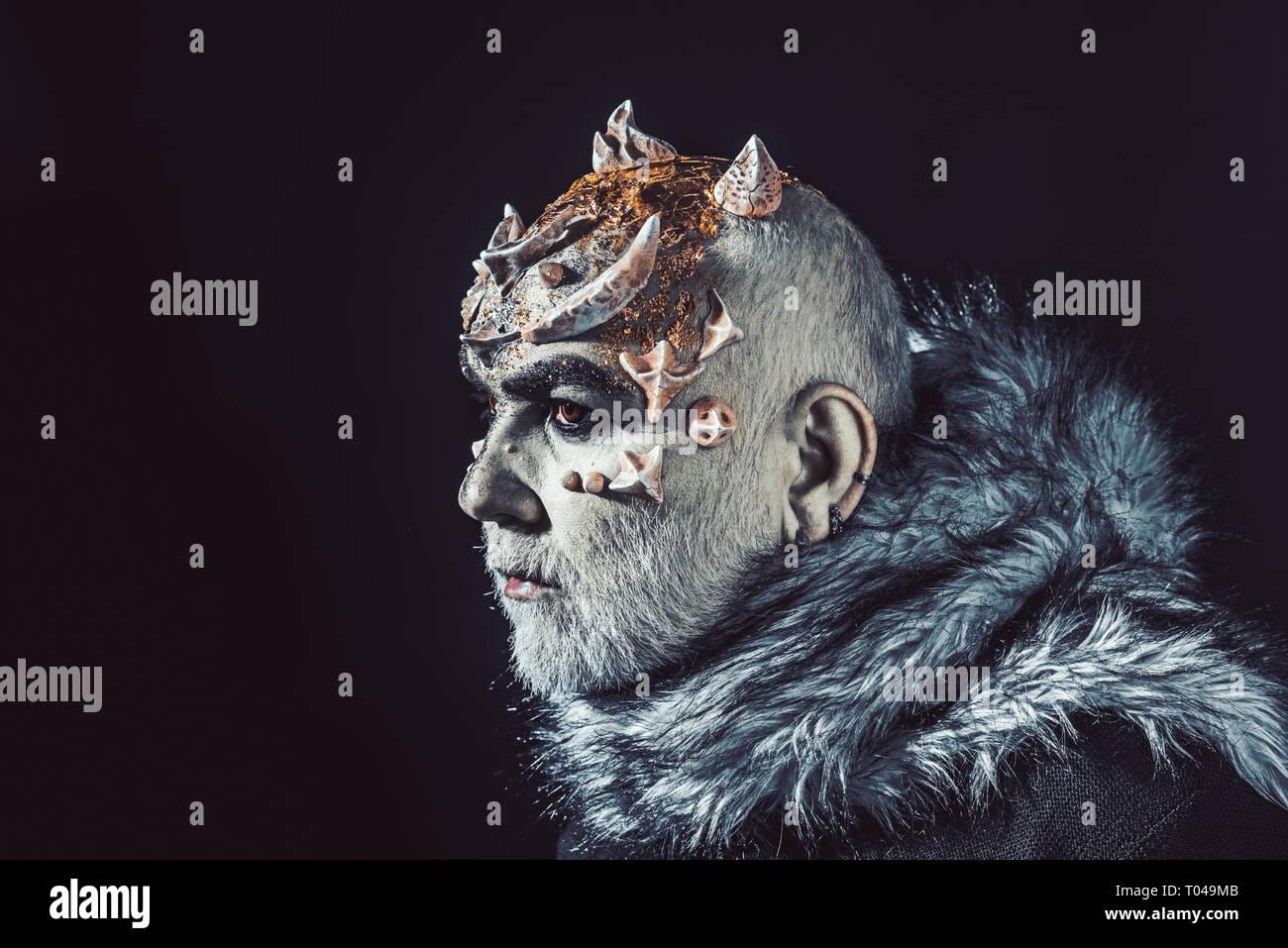 Alien, demon, sorcerer makeup. Demon on black background, copy space. Theatrical makeup concept. Senior man with white beard dressed like monster. Man - Stock Image