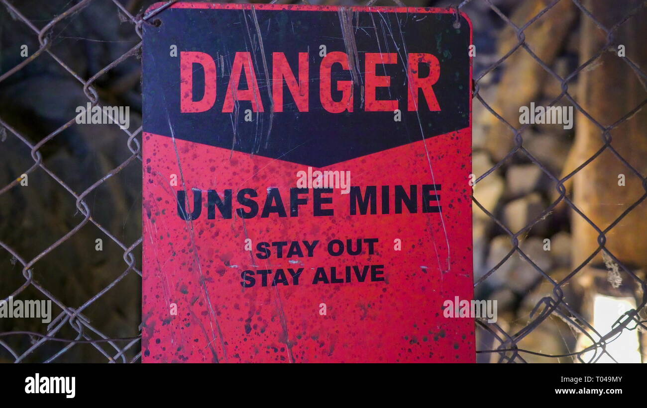 A danger sign on the gate outside a mining area a red sign that is found outside the gate - Stock Image