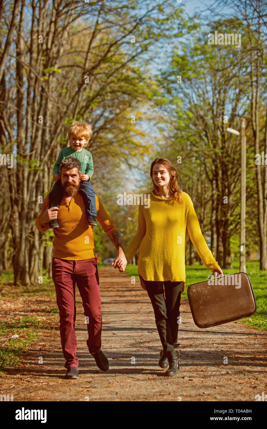 Leisure travelers of husband and wife with little son walk on park road. Traveler attraction. Take your bag and leave today - Stock Image
