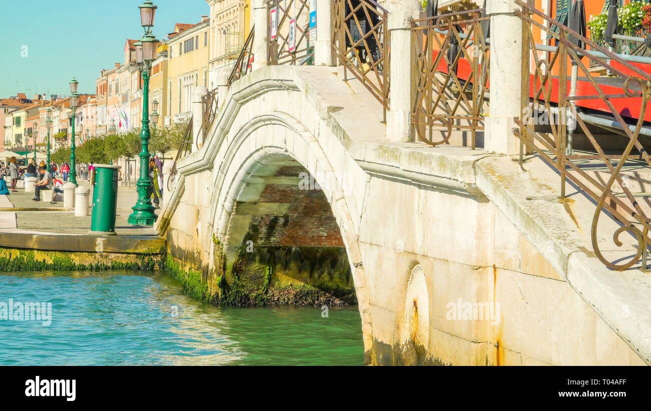 A small bridge across the small canal in Venice on a sunny morning in Venice Italy - Stock Image
