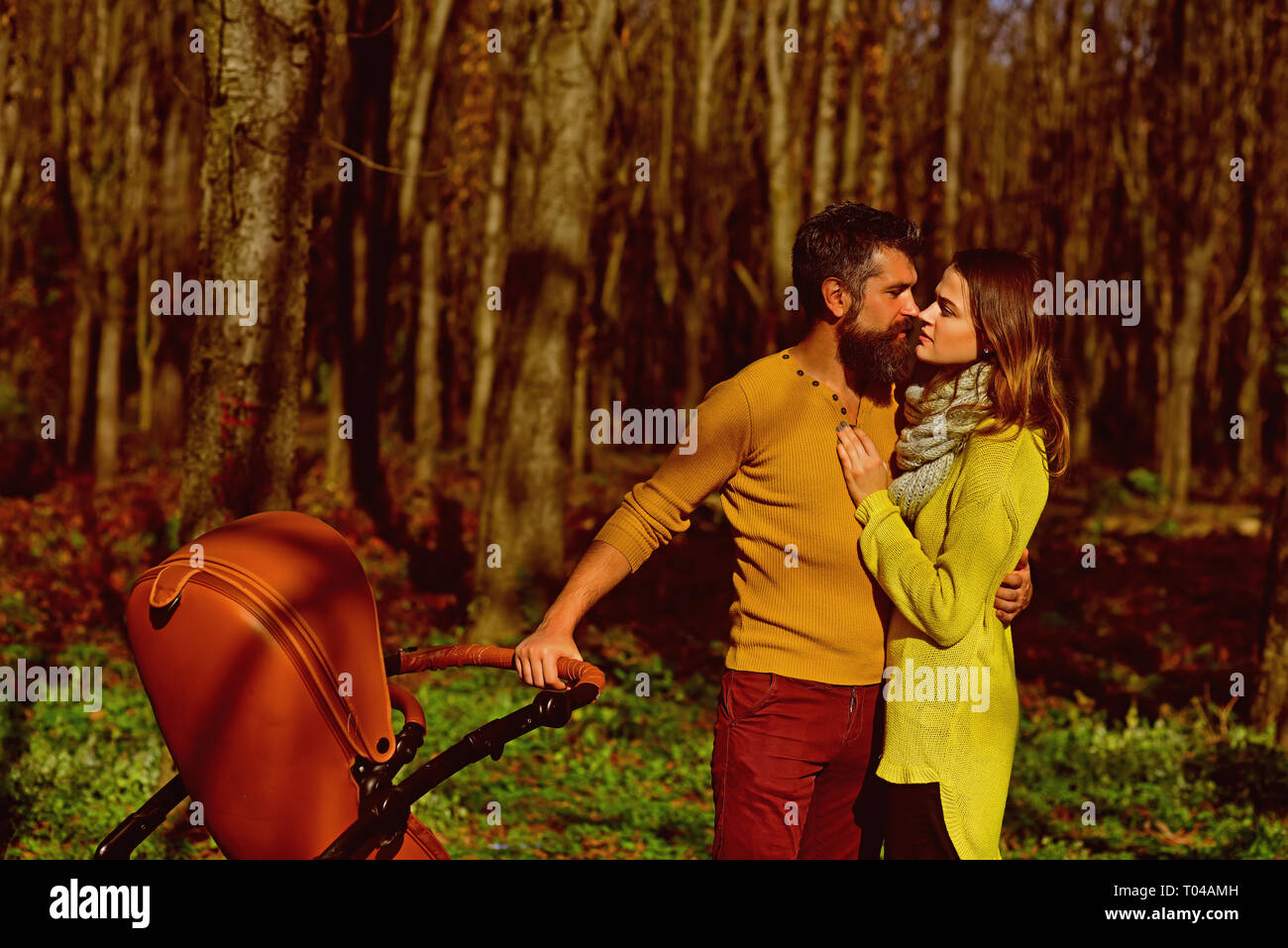 Couple in love kiss in pleasure park. Happy family with baby pram spend time with pleasure together. True love is a big deal - Stock Image