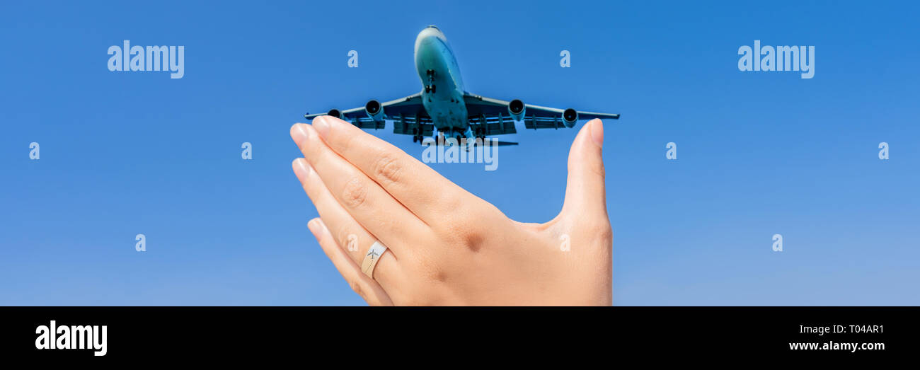 Female hand with a ring with a drawn plane holding a plane flying in the sky. Traveling on an airplane concept. Text space. Impressive paradise. Hot b - Stock Image